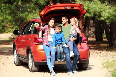 Happy family taking selfie near modern car outdoors