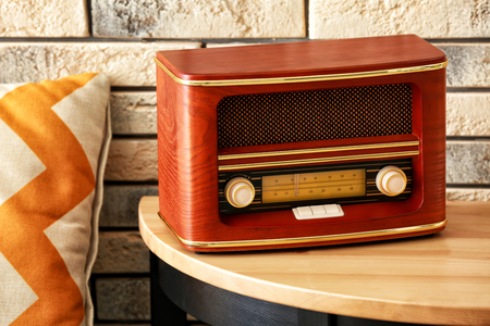 Radio receiver with retro design on table in room