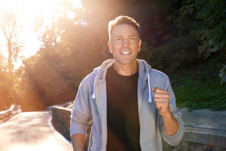 Mature sporty man running outdoors 스톡 콘텐츠
