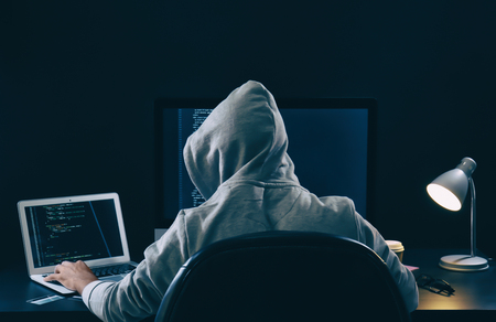 Man wearing hoodie hacking server in dark room 스톡 콘텐츠