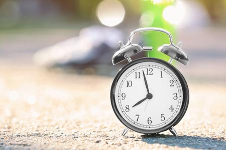 Alarm clock on asphalt outdoors. Morning routine concept