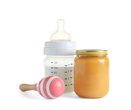 Jar with healthy baby food, bottle of milk and rattle on white background 写真素材