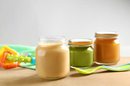 Jars with healthy baby food on wooden table Stock Photo