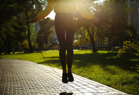 Sporty young woman jumping rope in park