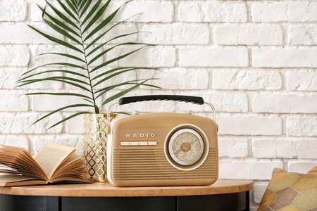 Retro radio on table against brick wall