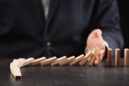 Man and domino pieces on table. Management concept Stock Photo
