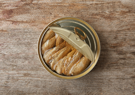 Open tin can with fish on wooden background
