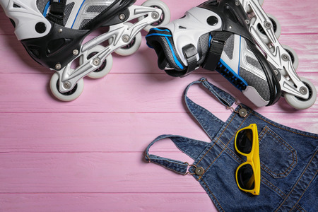 Roller skates, clothes and sunglasses on color wooden background