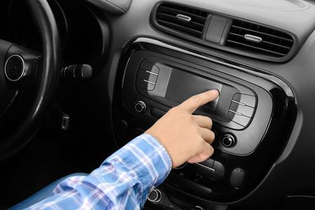 Man tuning radio in car 写真素材