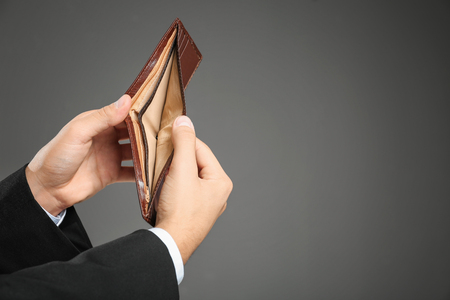 Hands of young businessman with empty purse on grey background