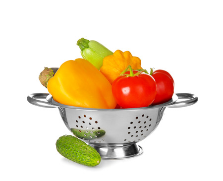 Colander with vegetables on white background 版權商用圖片