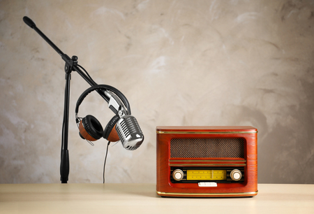 Retro radio, headphones and microphone on table against light wall Reklamní fotografie