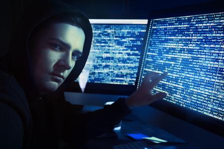Hacker using computer in dark room Stock Photo