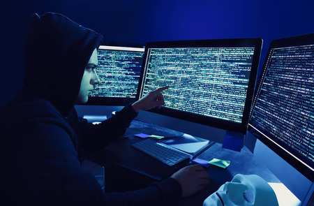 Hacker using computer in dark room Stock Photo - 113335707