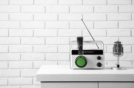Retro radio, headphones and microphone on table against brick wall