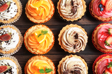 Tasty colorful cakes on wooden background, top view Stock fotó