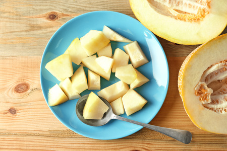 Plate with yummy melon on wooden table Stock Photo