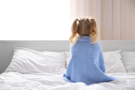 Cute little girl with towel on bed at home