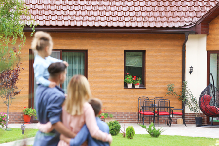 Happy family standing in courtyard and looking at their house Stockfoto - 111532853