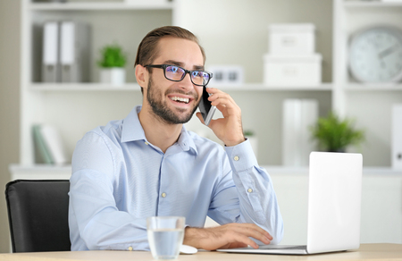 Attractive man with laptop talking on phone in office