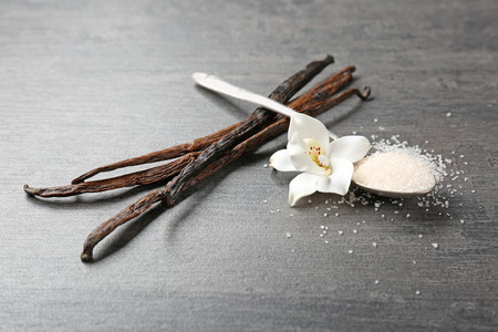Dried vanilla sticks, flower and sugar in spoon on wooden table