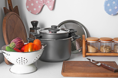 Cooking utensils and fresh vegetables on table in kitchen