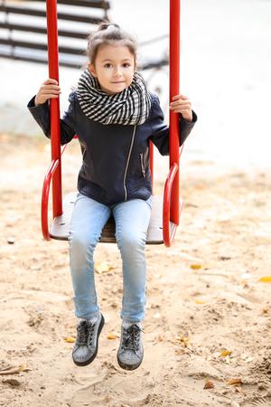 Cute little girl in outwear swinging outdoors