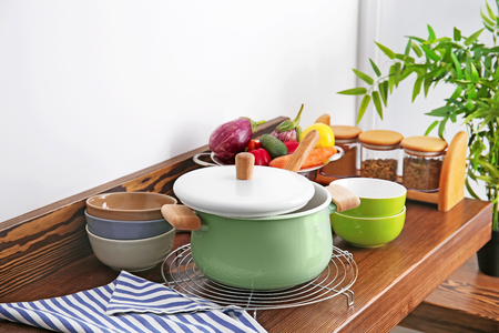 Stewpan, bowls and vegetables on wooden table in kitchen