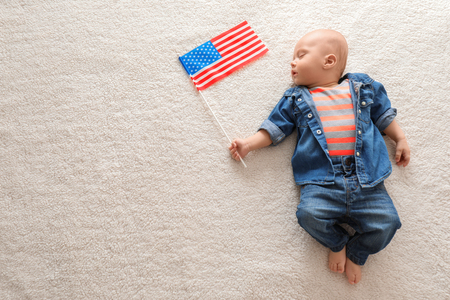 Cute baby with American flag on light background