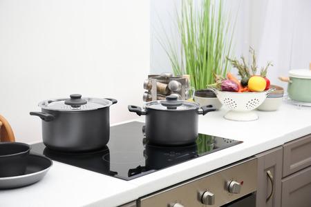 Kochutensilien auf Elektroherd in der Küche Standard-Bild