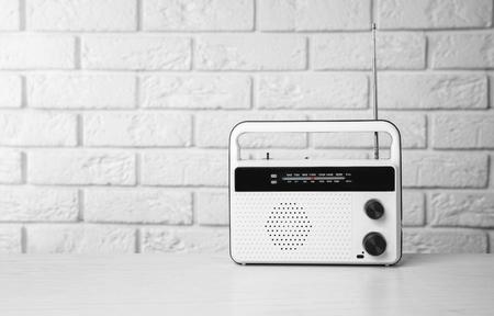 Retro radio on table near brick wall Imagens