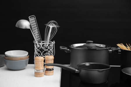 Different cooking utensils on electric stove against black background Imagens