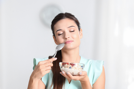 Young woman eating oatmeal on light background