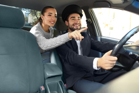 Young female passenger showing taxi driver the way