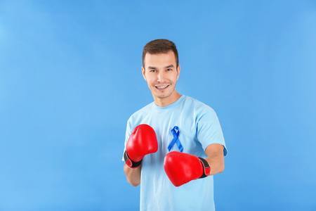 Young man in t-shirt with blue ribbon wearing boxing gloves on color background. Prostate cancer awareness concept