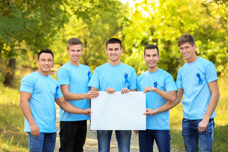Young men in t-shirts with blue ribbons holding blank banner outdoors. Prostate cancer awareness concept