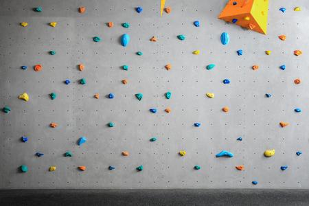 Graue Wand mit Klettergriffen in der Turnhalle