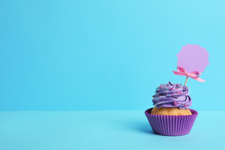 Tasty cupcake on table against color background Stock Photo