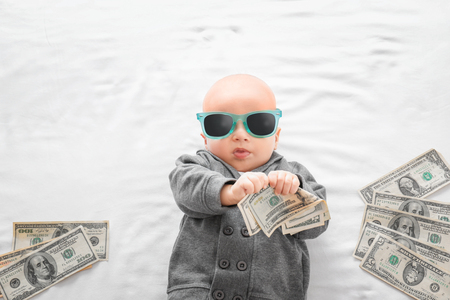 Cute boy with money on white bedsheet Foto de archivo