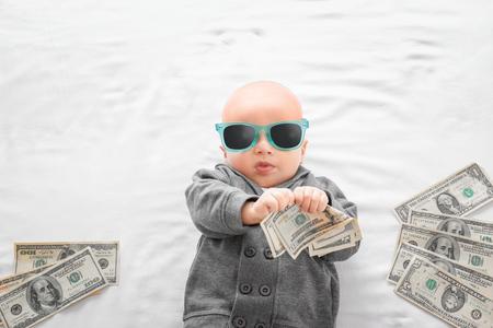 Garçon mignon avec de l'argent sur un drap blanc Banque d'images