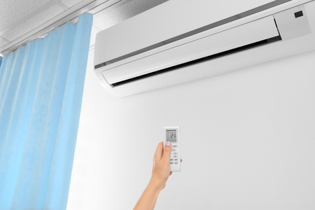 Female hand with remote control pointing at air conditioner indoors Фото со стока