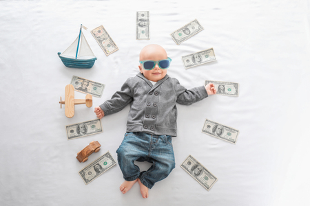 Cute boy with money and toys on white bedsheet