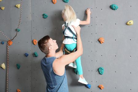 Lehrer hilft kleinem Mädchen beim Klettern an der Wand im Fitnessstudio Standard-Bild