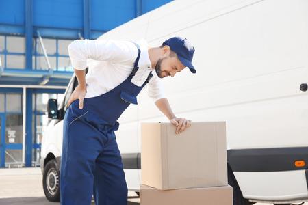 Lieferbote, der unter Schmerzen leidet, nachdem er eine schwere Kiste in der Nähe des Autos bewegt hat