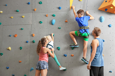 Instructors helping children climb wall in gym Stockfoto