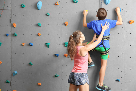 Instructor helping boy climb wall in gym Stok Fotoğraf