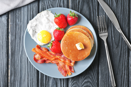 Tasty breakfast with pancakes, bacon and fried egg on table