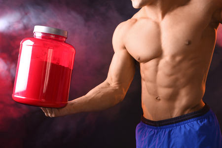 Sporty young man with jar of protein powder on dark background