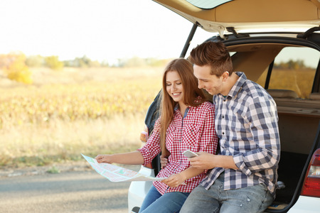Beautiful young couple sitting with map in car trunk Stockfoto