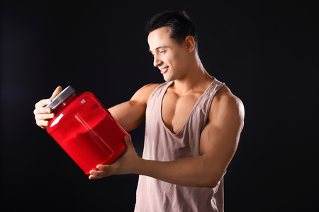 Sporty young man with jar of protein powder on black background